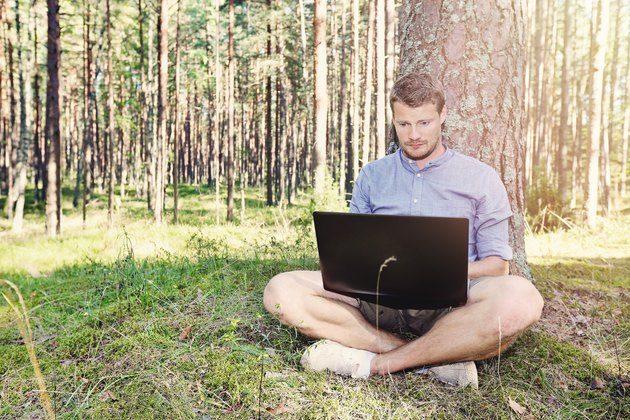 young man working with his laptop outdoors