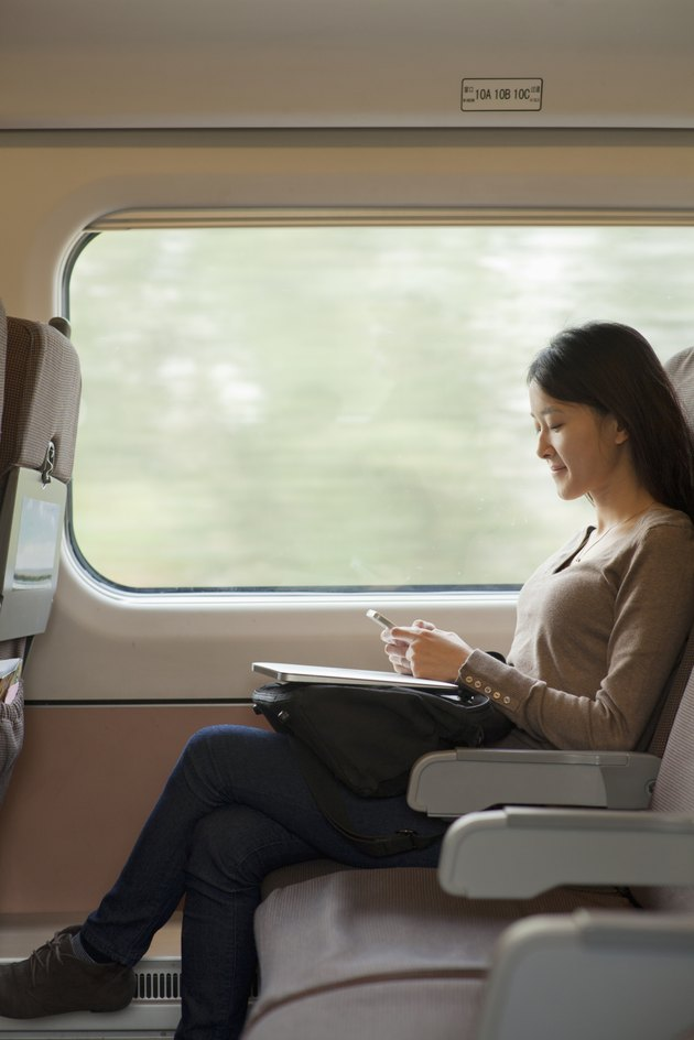 Young woman sitting on a train using her phone