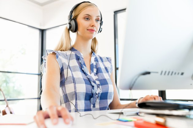 Young woman listening to the music while working on a