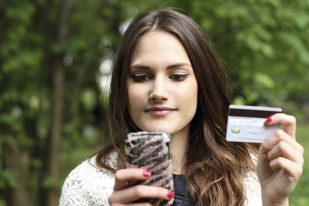 Beautiful girl with mobile phone and credit card
