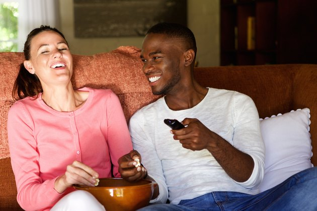 Happy young couple enjoying watching movie at home