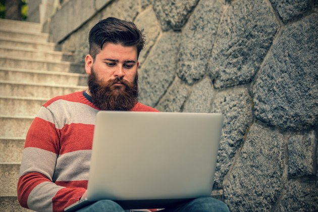 Young hipster sitting and using laptop