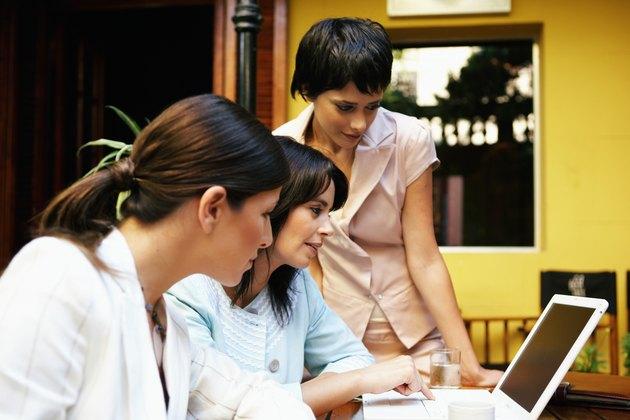 Three women having meeting in restaurant looking at laptop