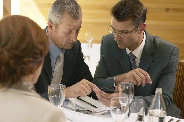 Two businessmen and businesswoman in restaurant, men using calculator