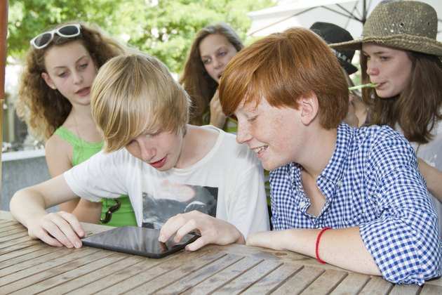 Teenage friends using digital tablet in pavement cafe