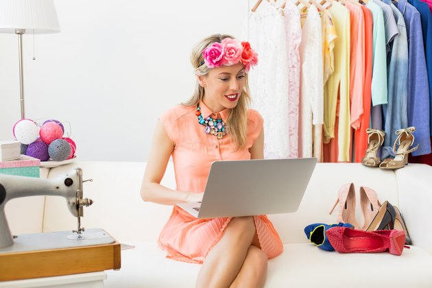 Fashion blogger sitting on couch and using computer