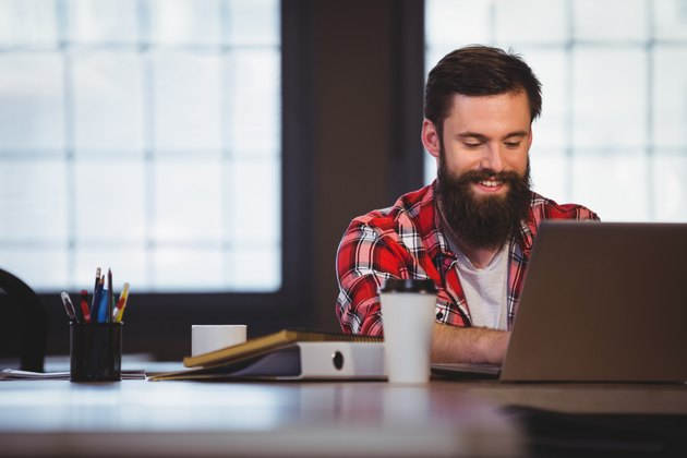 Hipster smiling while working on laptop
