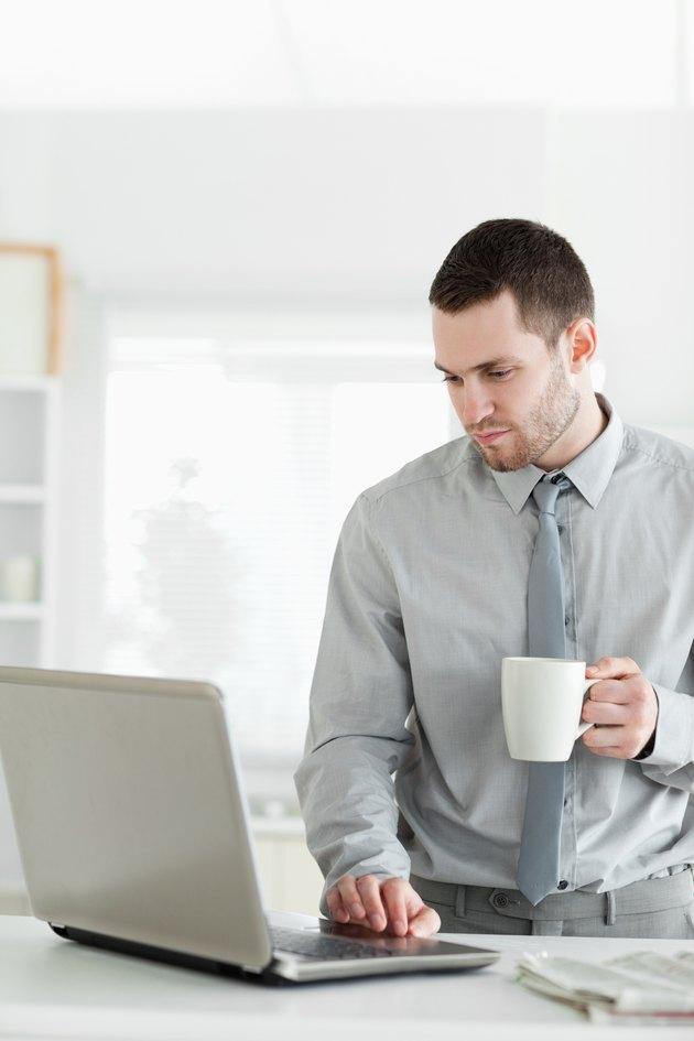 Portrait of a businessman using a notebook while drinking tea