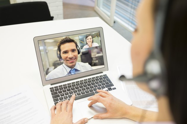 Businesswoman in the office on videoconference with headset, Skype