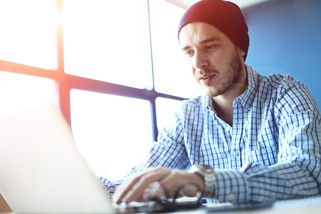 Handsome man working from his home office. Analyze business plans