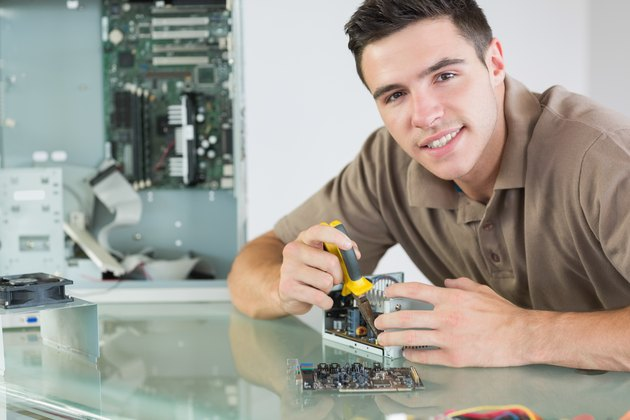 Handsome smiling computer engineer repairing hardware with pliers