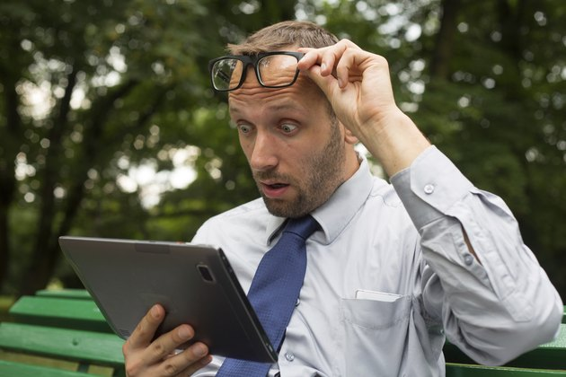 Businessman at the park with tablet sitting on a bench.