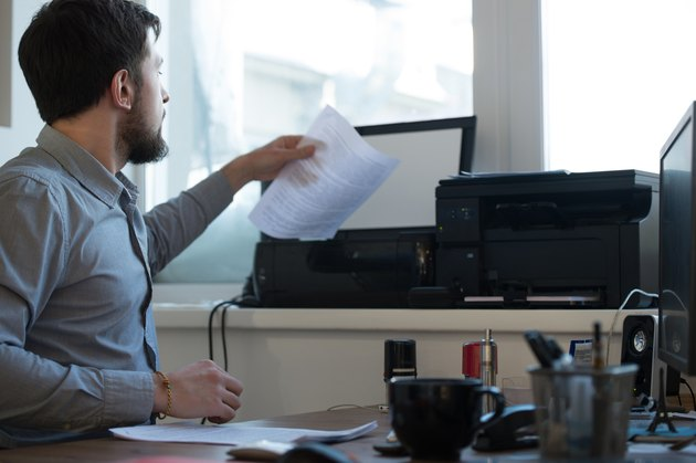 Handsome businessman scanning and printing document in office