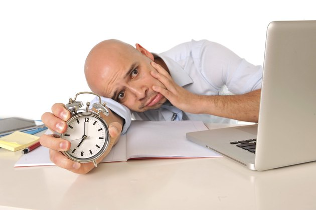 Overworked exhausted bald business man with computer and alarm clock