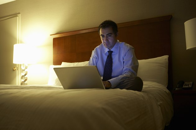 Business man sitting cross-legged on bed in hotel room working on laptop