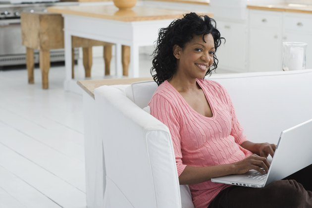 Woman sitting on couch and using laptop computer