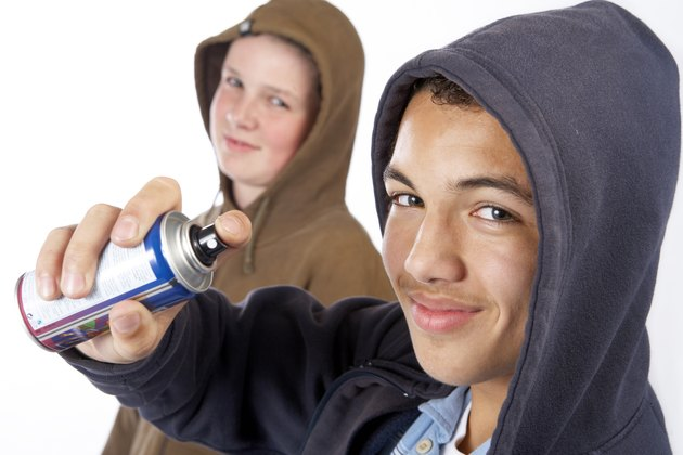 Teenage boys with can of spray paint