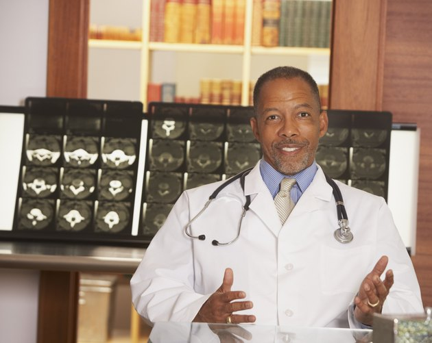 African American male doctor in front of MRIs