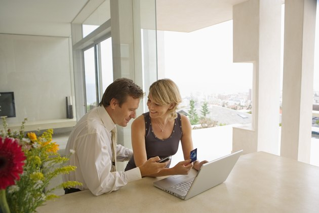Couple using laptop and cell phone