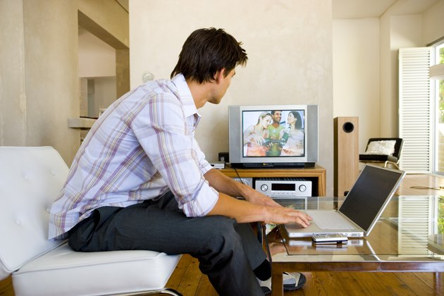 Man watching television with laptop