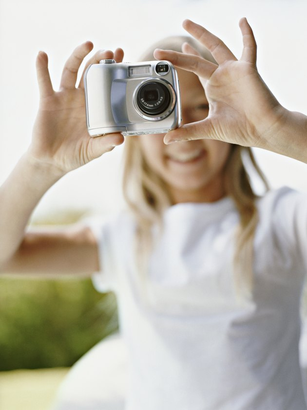 Young Girl Takes a Picture With a Digital Camera, Focus on the Camera in the Foreground