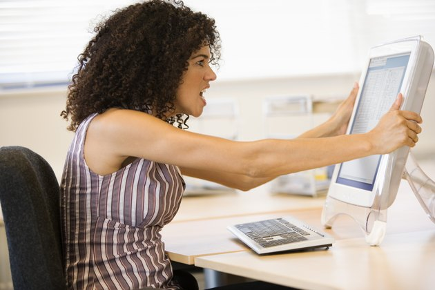 Businesswoman shaking computer