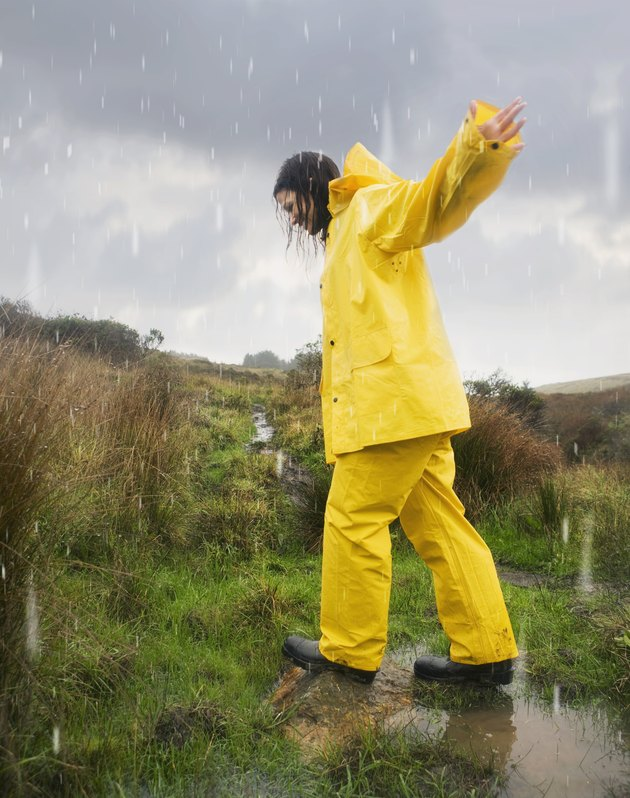 Hispanic woman in rain gear walking in puddle