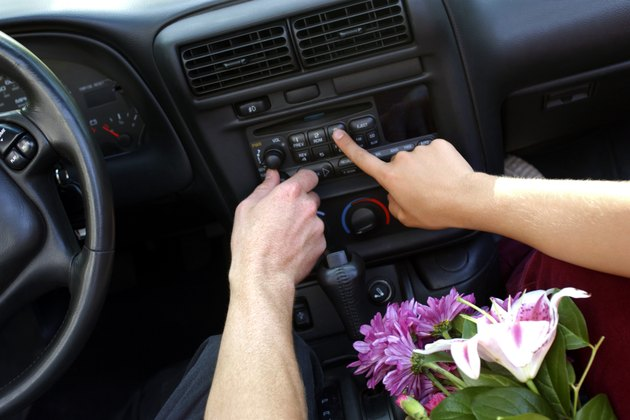 Close-up of two hands pressing buttons to adjust the car stereo.