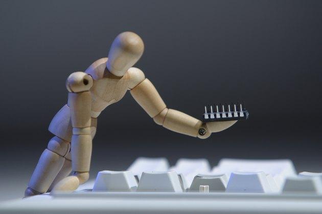 Figurine fixing broken keyboard