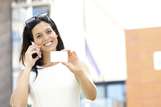 Casual businesswoman showing visiting card