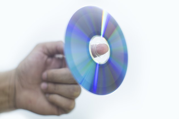 Holding a disc with finger white bckground