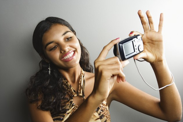 Young woman with camera taking picture of herself