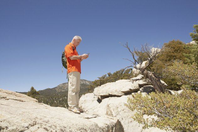 Mature Man in mountains using cell phone