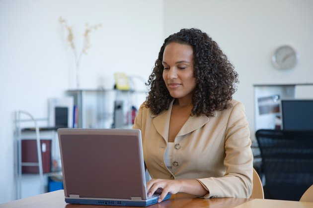 Businesswoman working at laptop on table in office