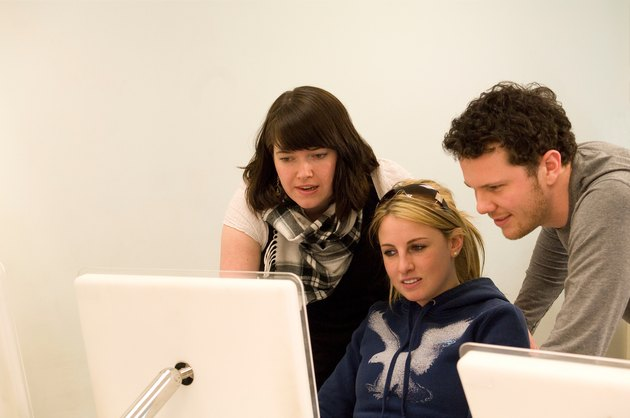 Group of three graphic design students working together on a mac computer.