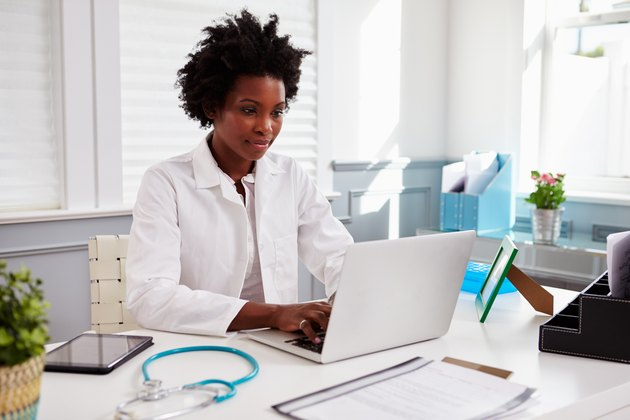 Black female doctor wearing white coat at work in
