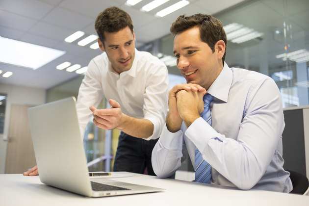 Two handsome businessmen working together on a project at office
