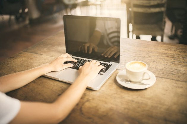 Girl typing on a laptop keyboard in a cafe