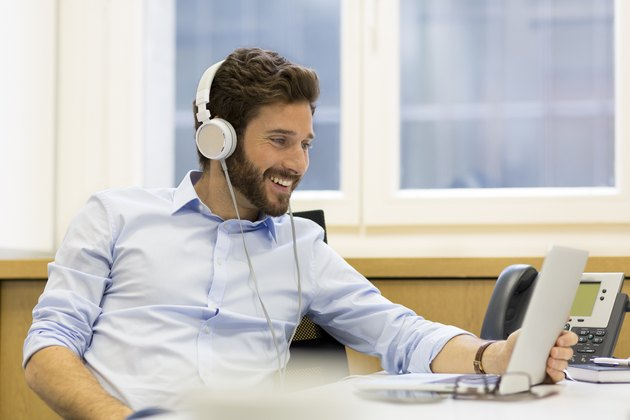 Cheerful man listening music and using computer in modern office