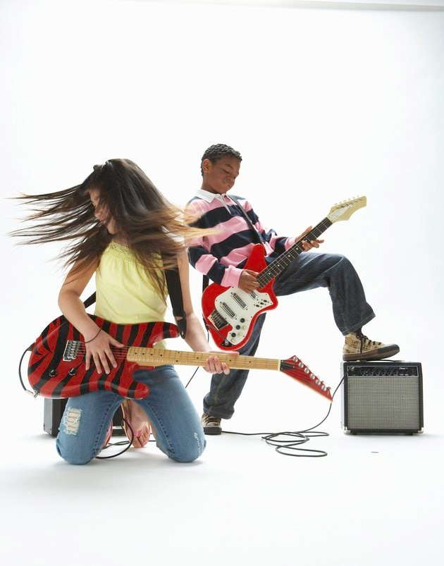 Boy and girl (9-11) playing electric guitars
