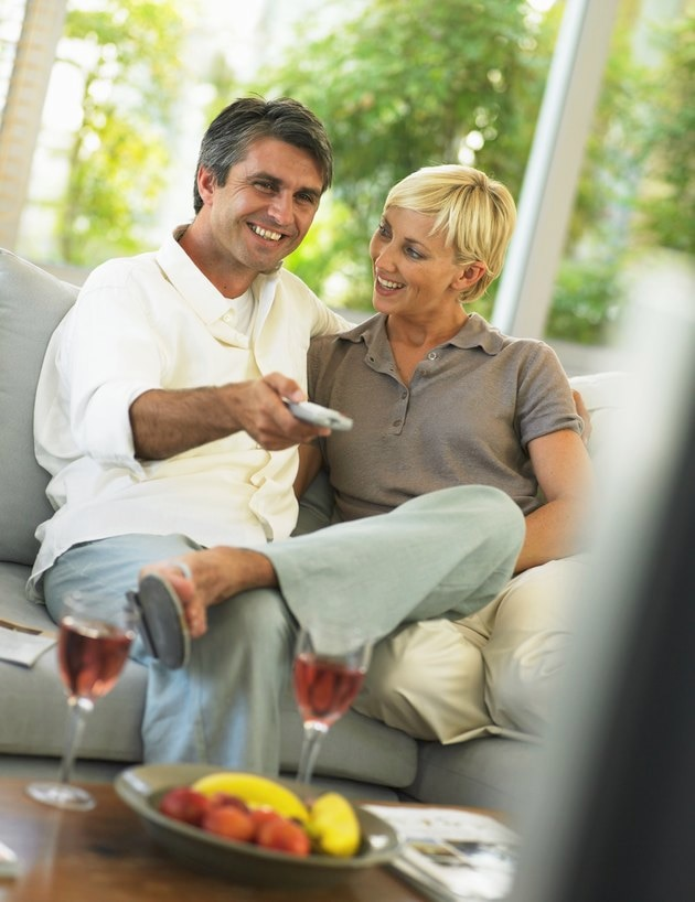 Couple sitting on sofa, man holding remote control, smiling