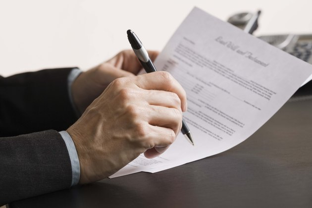 Person writing on paper documents