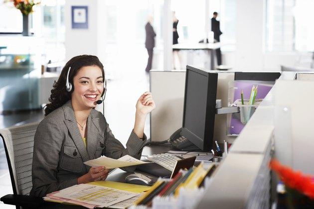 Businesswoman wearing headset at desk, smiling, portrait