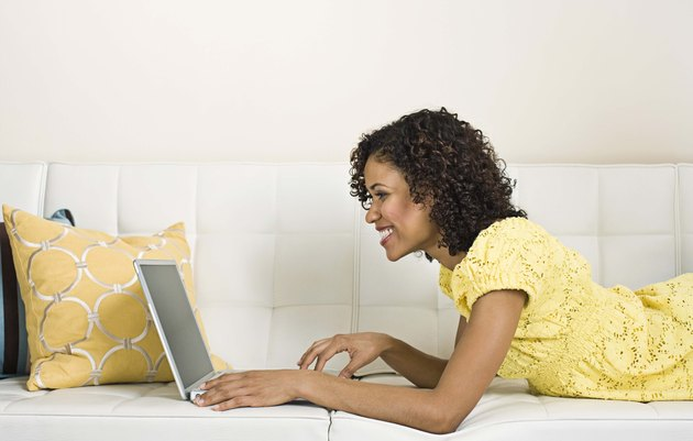 Woman with laptop on couch