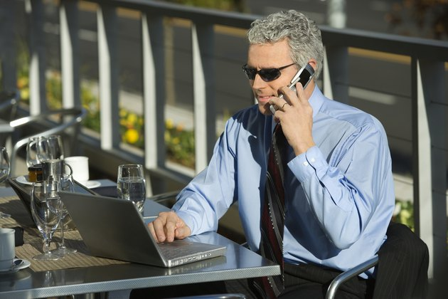 Prime adult Caucasian man in suit sitting at patio table outside looking at laptop and talking on cellphone.