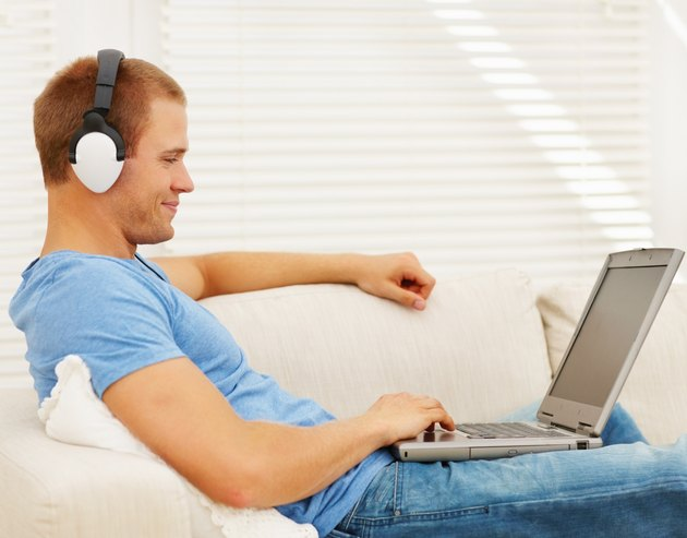 Smart young man listening to music while using a laptop