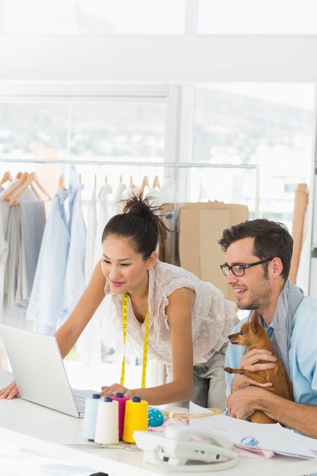Fashion designers using laptop in studio