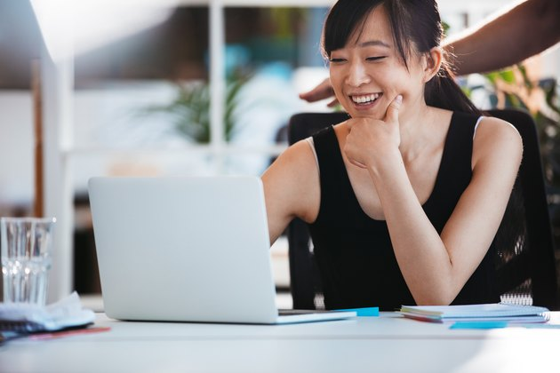Smiling woman working on laptop at office