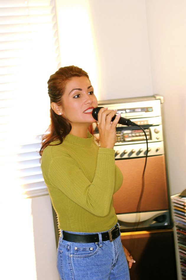 Portrait of a woman singing into a microphone.