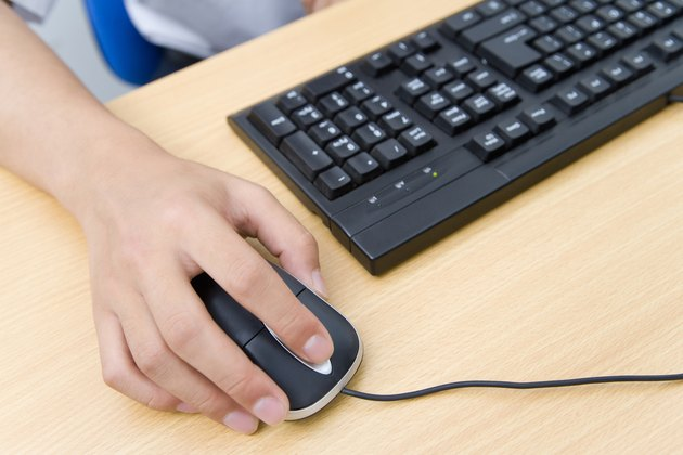 Hand on computer mouse, China, Beijing